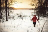 Finland, Kuopio, toddler girl walking in winter landscape at sunset - PSIF00263