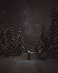 Finland, Kuopio, woman walking under milky way in winter forest - PSIF00266