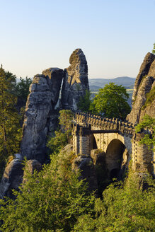 Germany, Saxony, Elbe Sandstone Mountains, view to the Bastei rock formation at sunrise with Bastei Bridge - RUEF02197
