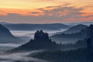 Germany, Saxony, Elbe Sandstone Mountains, view to the mountain Winterstein from the Gleitmannshorn at sunrise - RUEF02203