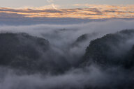 Germany, Saxony, Elbe Sandstone Mountains, view from Gleitmannshorn to sandstone rocks with fog at sunrise - RUEF02218