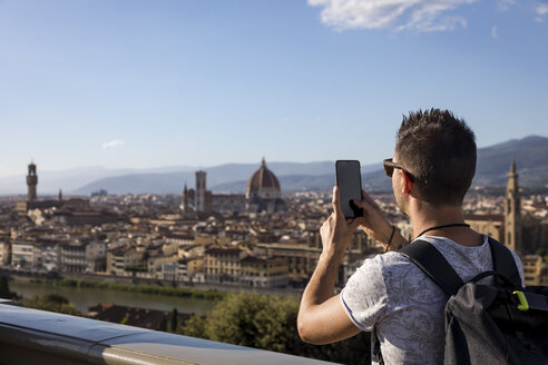 Man taking a photo of Florence with his smartphone, Florence, Italy - MAUF02454