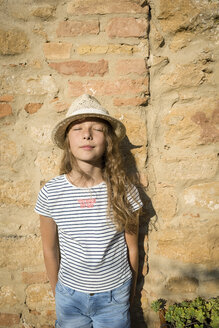Italy, Tuscany, Girl with straw hat leaning on wall eyes closed - OJF00340