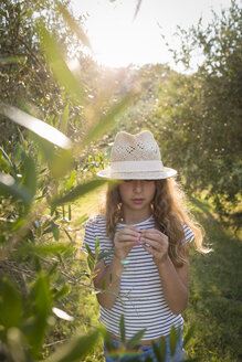 Italy, Tuscany, Girl with straw hat standing in an olive grove - OJF00346