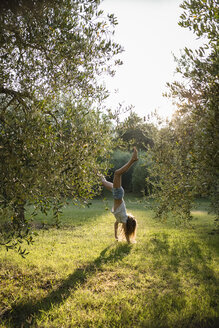 Girl doing handstand on a meadow, Tuscany, Italy - OJF00349