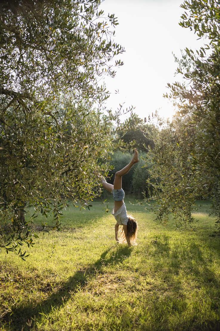 Girl doing handstand on a meadow, Tuscany, Italy - OJF00349 - Julia Otto/Westend61