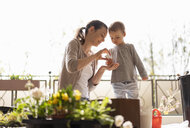 Mother and daughter planting flowers together on balcony - DIGF07034