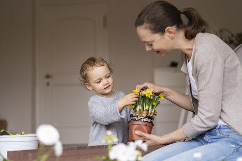 Mother and daughter planting flowers together on balcony - DIGF07040