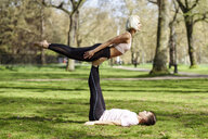 Young couple doing yoga acrobatics in an urban park - JSMF01075