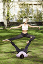 Young couple doing yoga acrobatics in an urban park - JSMF01078