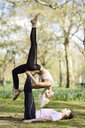Young couple doing yoga acrobatics in an urban park - JSMF01081