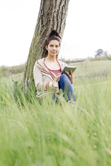 Young woman sitting at a tree in the countryside using tablet - HMEF00369