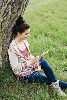 pretty, young woman with black hair sitting in a green meadow, leaning against a tree and working with her tablet, lower austria, austria - HMEF00372