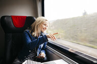 Smiling blond woman travelling by train looking out of window - HMEF00374