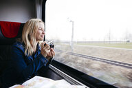 Happy blond woman with camera travelling by train looking out of window - HMEF00383