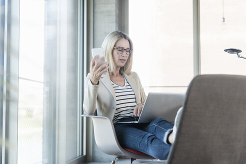 Relaxed businesswoman using laptop in office with feet up - UUF17466