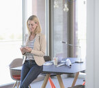 Smiling businesswoman using cell phone in office - UUF17475