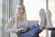 Relaxed businesswoman using laptop in office with feet up - UUF17478