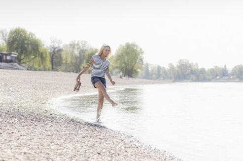 Carefree mature woman splashing in a river - UUF17586