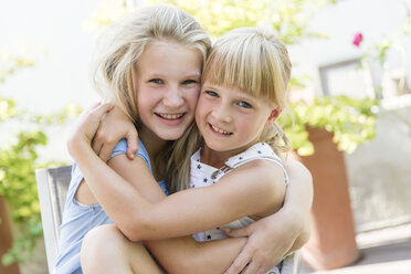 Portrait of two girls hugging outdoors - SHKF00805