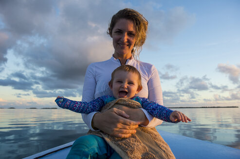French Polynesia, Tuamotus, Tikehau, mother holding her happy baby in a boat on the ocean - RUNF02078