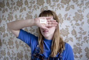 Student holding a hand in front of her eyes, a note with the word fear on her hand - FLLF00182
