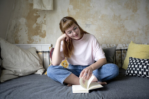 Female student reading a book in her room - FLLF00200