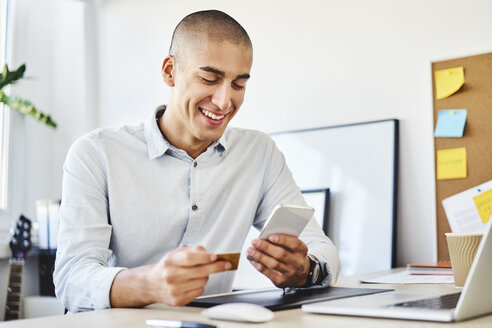 Young man sitting in home office paying online with credit card and smartphone - BSZF01075