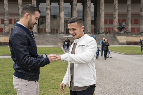 Young man putting on ring to his happy boyfriend at Lustgarten, Berlin, Germany - TAMF01499