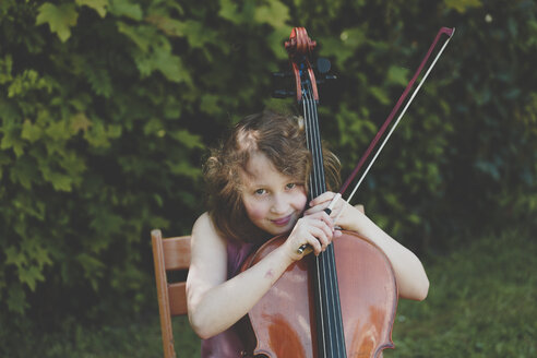 A girl playing the cello in garden, looking at camera - IHF00031