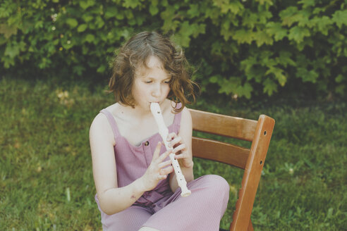 A girl playing the flute in the garden - IHF00034