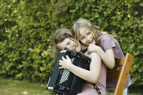 Girl with accordion and her sister, bonding with each other - IHF00037