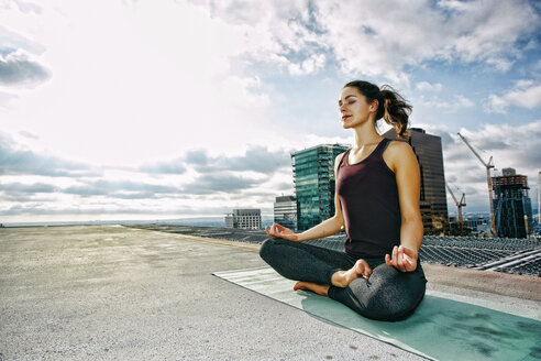 Caucasian woman meditating on urban rooftop - BLEF03832