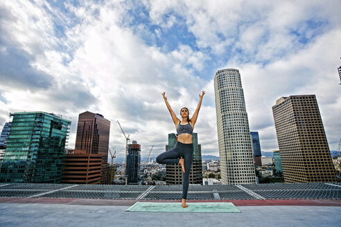 Caucasian woman doing yoga urban rooftop - BLEF03835