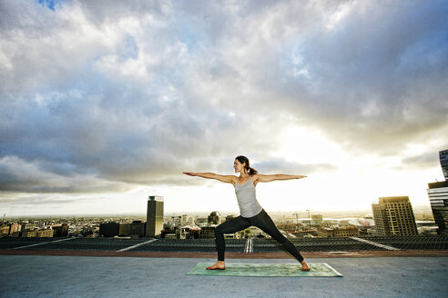 Caucasian woman stretching on urban rooftop - BLEF03847