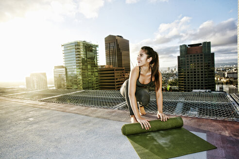 Caucasian woman rolling exercise mat on urban rooftop after yoga - BLEF03853