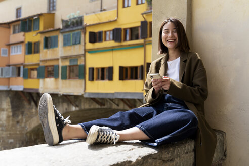 Italy, Florence, happy young woman resting on a wall in the city - FMOF00614