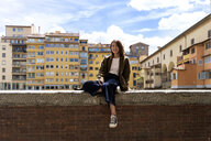 Italy, Florence, smiling young woman resting on a wall in the city - FMOF00617