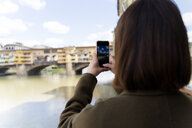 Italy, Florence, young tourist woman taking a cell phone picture at Ponte Vecchio - FMOF00626