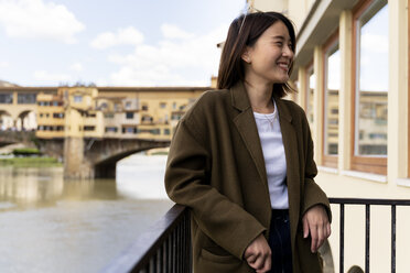 Italy, Florence, happy young tourist woman at Ponte Vecchio - FMOF00629