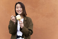 Happy young woman eating an ice cream cone at an orange wall - FMOF00632