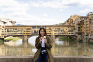 Italy, Florence, young tourist woman eating an ice cream cone at at Ponte Vecchio - FMOF00638