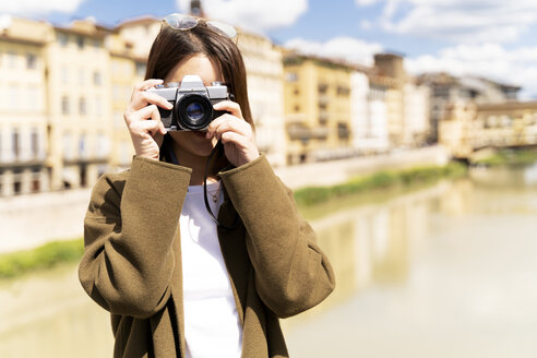 Italy, Florence, young tourist woman taking pictures at Ponte Vecchio - FMOF00641