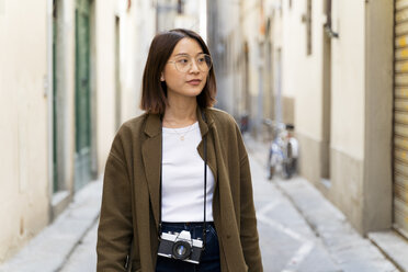 Italy, Florence, young woman strolling in an alley - FMOF00644