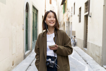 Italy, Florence, happy young woman with earphones and cell phone in an alley - FMOF00647