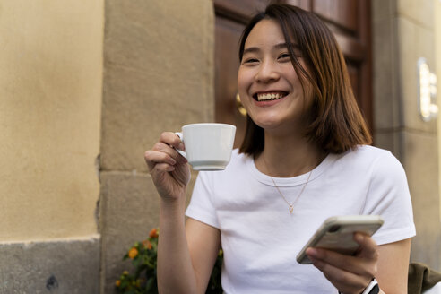 Italy, Florence, happy young woman with cell phone at an outdoor cafe - FMOF00653