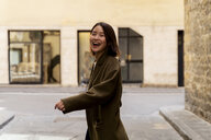 Italy, Florence, happy young woman in the city - FMOF00659