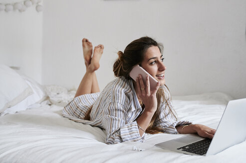 Young woman lying in bed, using laptop, talking on the phone - IGGF01165