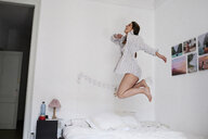 Young woman jumping for joy on her bed - IGGF01168