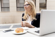 Businesswoman drinking coffee at pavement cafe - FMOF00678
